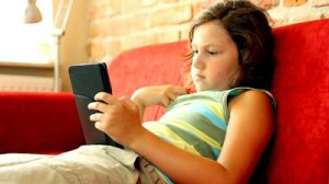 stock-footage-young-teenager-with-ebook-reader-on-sofa-camera-stabilizer-shot